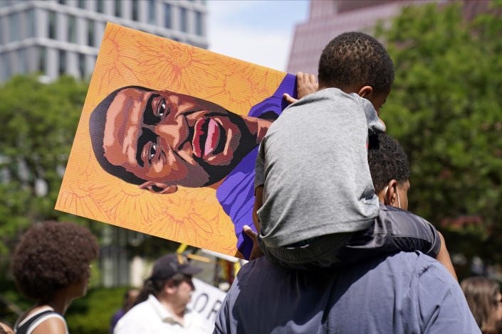 A young boy holds a George Floyd poster as he sits on a shoulder after former Minneapolis police officer Derek Chauvin was sentenced to 22 1/2 years in prison for the May 2020 murder of Floyd, Friday, June 25, 2021, in Minneapolis. (AP Photo/Jim Mone)