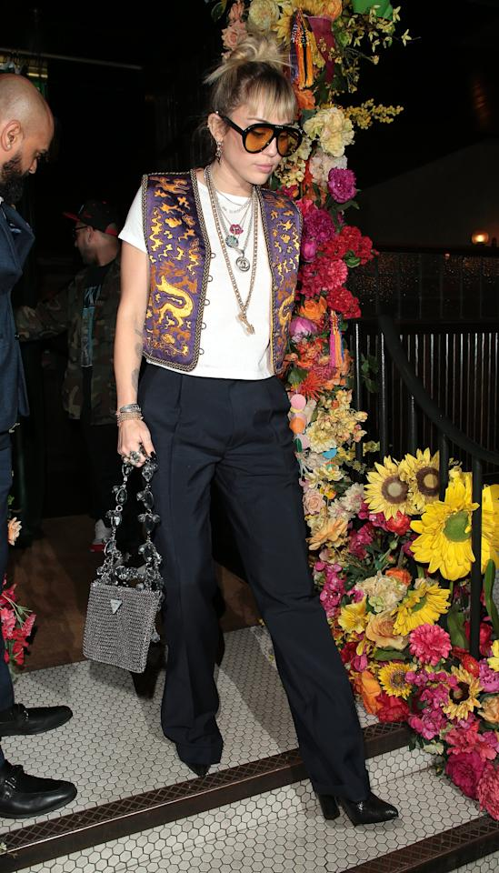 <p><strong>How to get the look</strong>: Wear long black trousers with heeled booties, a white t-shirt, and layered necklaces. Top with funky sunglasses and a vintage-inspired vest.</p>