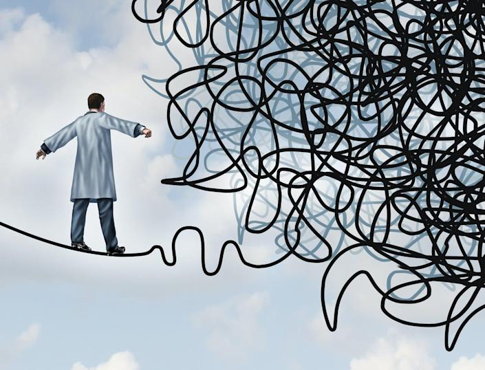 A doctor walks along a tightrope towards a jumbled knot of rope.