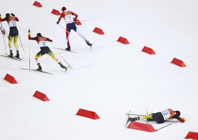 (L to R) Germany's Bjoern Kircheisen, Norway's Magnus Hovdal Moan, Germany's Fabian Riessle ski ahead of Germany's Johannes Rydzek, who crashes, in the cross country race of the Nordic Combined individual Gundersen 10 km event of the Sochi 2014 Winter Olympic Games, at the RusSki Gorki Ski Jumping Center in Rosa Khutor, February 18, 2014. REUTERS/Kai Pfaffenbach (RUSSIA - Tags: OLYMPICS SPORT SKIING)
