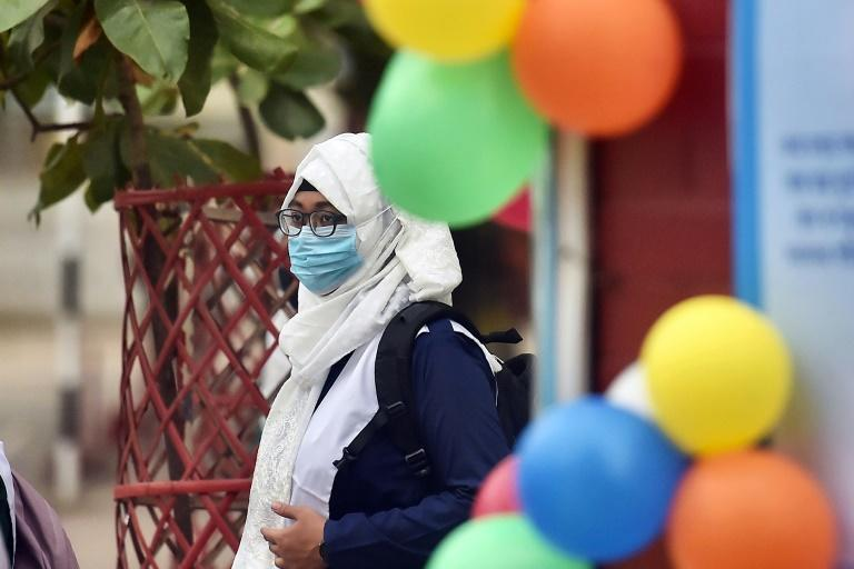 One school in Dhaka welcomed students with flowers and sweets, and asked them to wear masks and sanitise their hands (AFP/Munir Uz zaman)