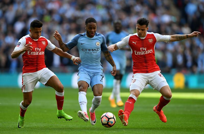 Raheem Sterling (C) of Manchester City controls the ball under pressure of Alexis Sanchez (L) and Granit Xhaka (R) of Arsenal during the Emirates FA Cup Semi-Final match between Arsenal and Manchester City at Wembley Stadium