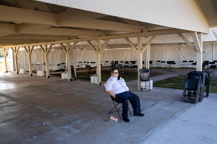 Security guard Andrea Rapini sits at a COVID-19 vaccination site that closed after running out of the vaccine in John Prince Park in Lake Worth Beach, Fla., on Jan. 27. Gov. Ron DeSantis turned  vaccine distribution over to Publix pharmacies in the area.