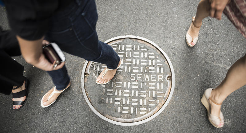A group of women walking walk over a sewer manhole cover.