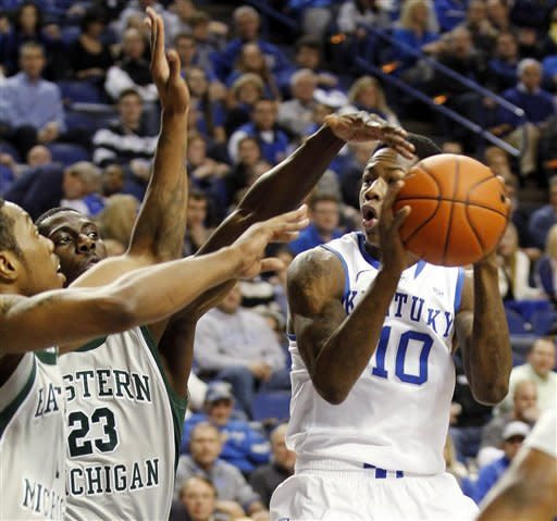 Kentucky's Archie Goodwin, right, shoots under pressure from Eastern Michigan's Da'Shonte Riley, left, and Glenn Bryant (23) during the first half of an NCAA college basketball game at Rupp Arena in Lexington, Ky., Wednesday, Jan. 2, 2013. (AP Photo/James Crisp)