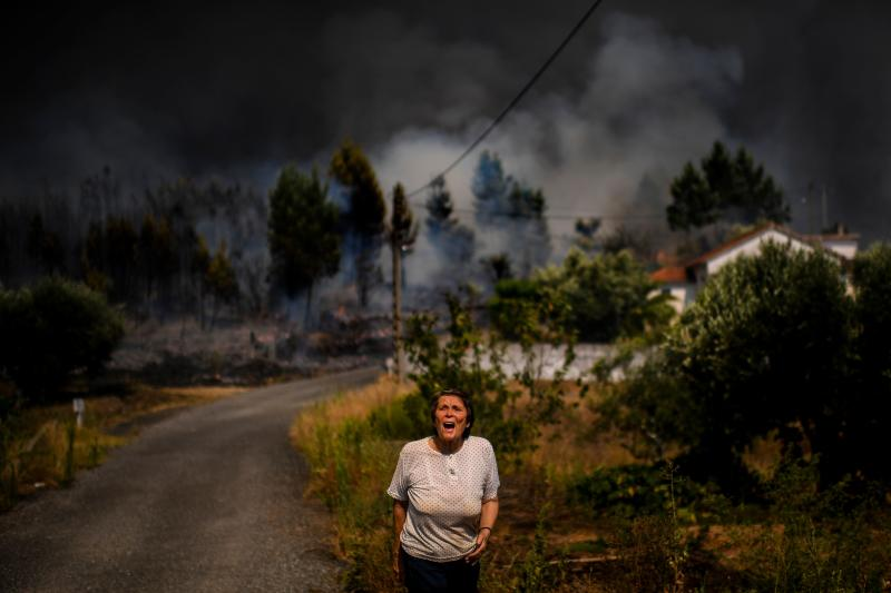 A villager shouts for help as a wildfire approaches a house at Casas da Ribeira village in Macao, central Portugal on July 21, 2019. (Photo: Patricia De Melo Moreira/AFP/Getty Images)