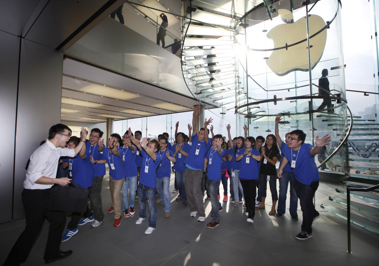 A customer cheers with staff members of Apple Inc. as the Apple store in Hong Kong started selling iPhone 5 Friday, Sept. 21, 2012. Apple's Asian fans jammed the tech juggernaut's shops in Australia, Hong Kong, Japan and Singapore to pick up the latest version of its iPhone. (AP Photo/Kin Cheung)