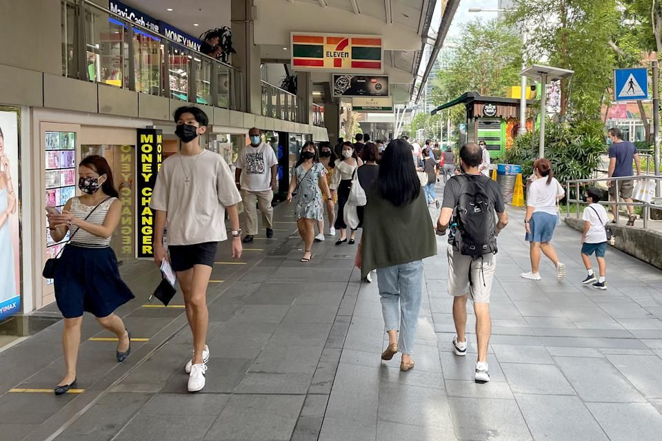 People seen walking along Orchard Road, in front of the Lucky Plaza mall, on 15 May 2021. (PHOTO: Dhany Osman / Yahoo News Singapore)