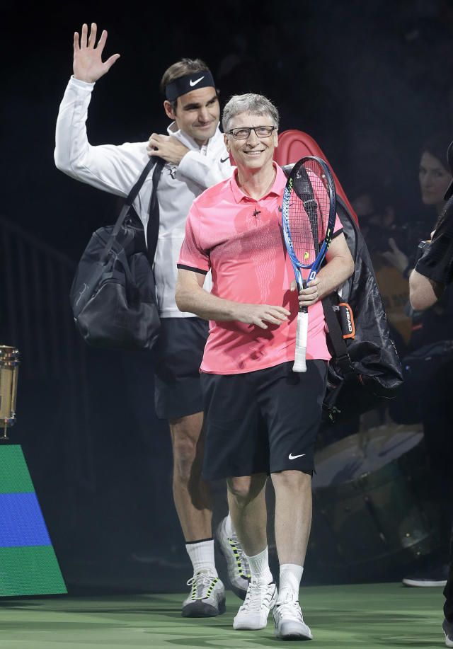 Bill Gates, foreground, and his partner Roger Federer, of Switzerland, walk onto the court before playing in an exhibition tennis match against Jack Sock and Savannah Guthrie in San Jose, Calif., Monday, March 5, 2018. (AP Photo/Jeff Chiu)