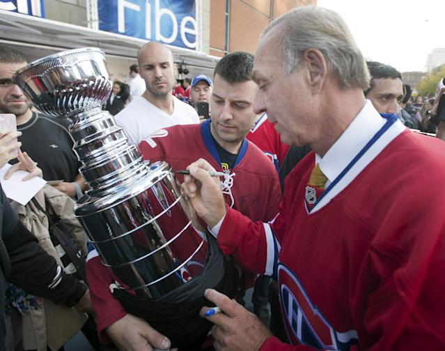 Montreal Canadiens hockey legend Guy Lafleur signs a Stanley Cup replica for Mario Fargnoli before the season-opening NHL hockey game between the Toronto Maple Leafs and the Montreal Canadiens, Tuesday, Oct. 1, 2013, in Montreal. (AP Photo/The Canadian Press, Ryan Remiorz)