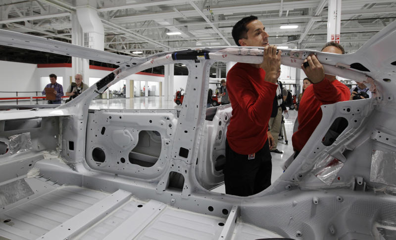 A worker inspects a Tesla Model S car at the Tesla factory in Fremont, Calif., Friday, June 22, 2012. The first Model S sedan car will be rolling off the assembly line on Friday. (AP Photo/Paul Sakuma)