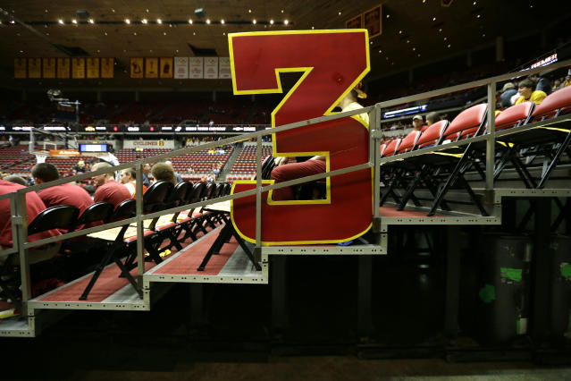 FILE - In this Jan. 17, 2015, file photo, a large 3-point sign sits in the stands before an NCAA college basketball game between Iowa State and Kansas, in Ames, Iowa. The NCAA Playing Rules Oversight Panel announced Wednesday that the arc will be moved to 22 feet, 1 3/4 inches for the 2019-20 season, matching the international distance. (AP Photo/Charlie Neibergall, File)