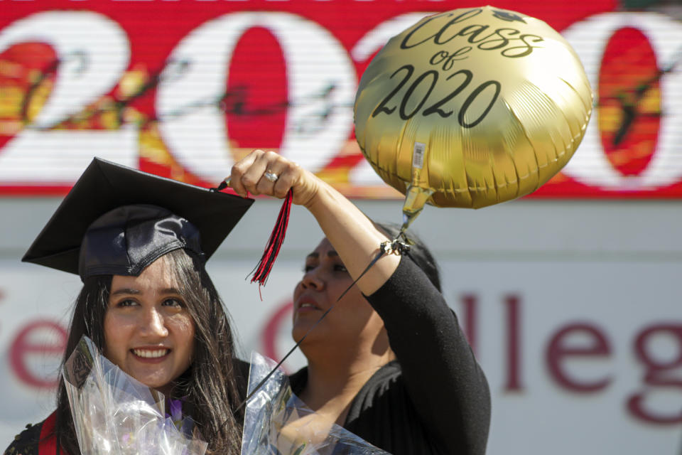RANCHO CUCAMONGA, CA - MAY 20: Melissa Gomes, right, fixes the tassel as new graduate Sarah Anggraini gets ready for a photo at the marquee of Chaffey Colleges that held a drive through graduation on Wednesday, May 20, 2020 in Rancho Cucamonga, CA. (Irfan Khan / Los Angeles Times via Getty Images)