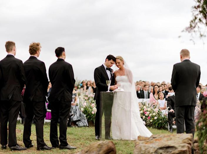 A bride and groom stand side by side in front of a crowd of family and friends outside under an overcast sky (Courtesy of Ashley Alexander Photography)