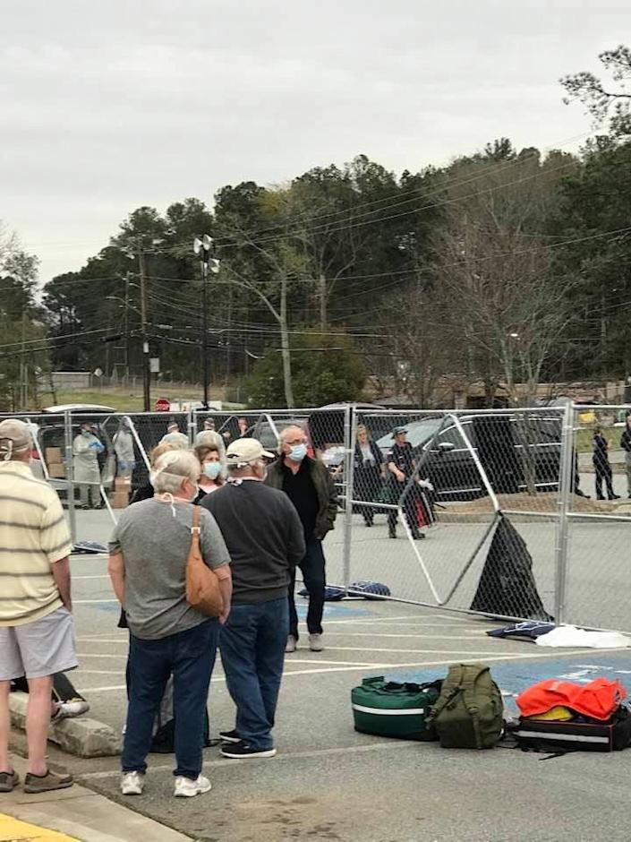 A barricade fence separates passengers from the Grand Princess cruise ship under federal quarantine at Dobbins Air Reserve Base in Georgia.