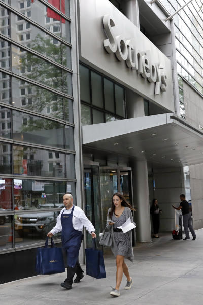 A Sotheby's worker carries bags outside the auction house, in New York, Monday, June 17, 2019. BidFair USA is taking auction house Sotheby's private in a deal valued at $3.7 billion. (AP Photo/Richard Drew)