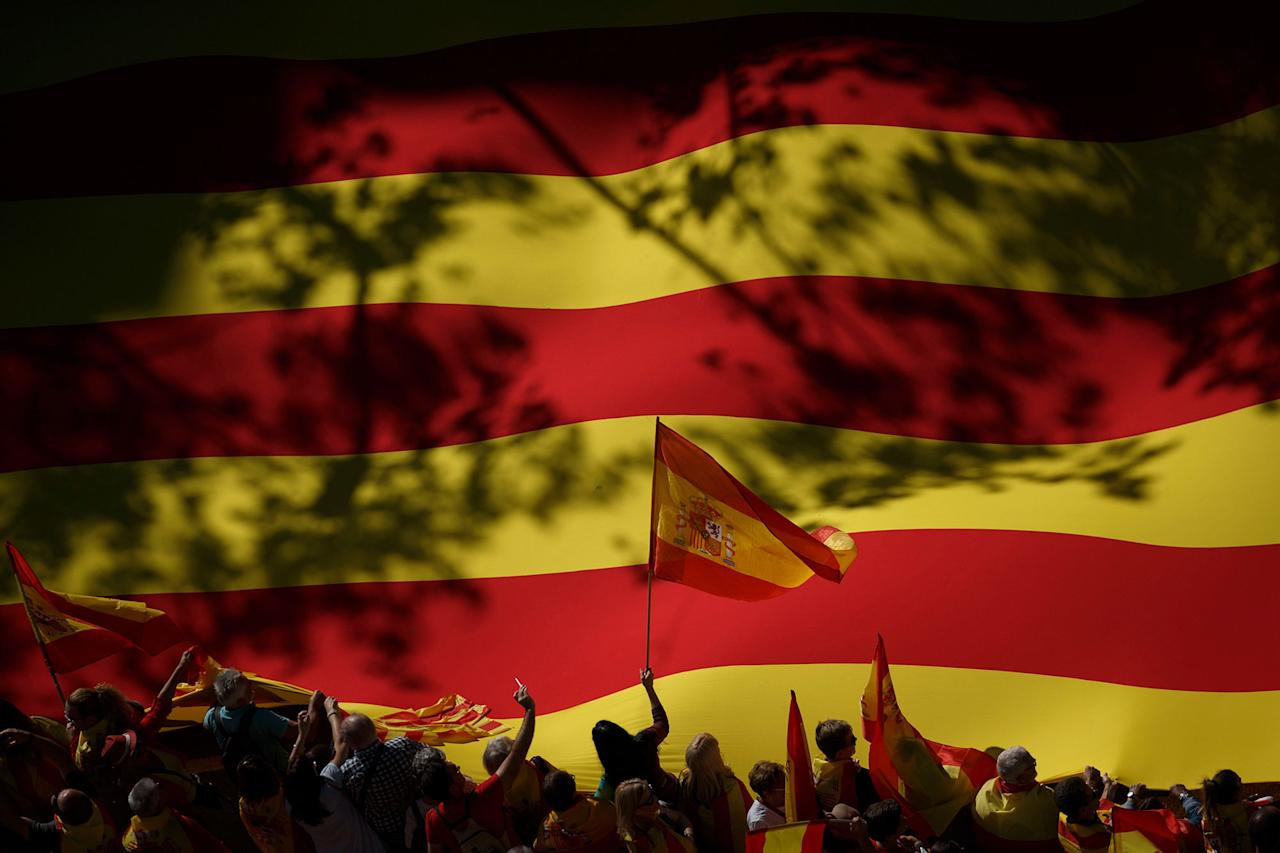 <p>A nationalist activist waves a Spanish flag in front of a giant Catalan flag during a mass rally against Catalonia's declaration of independence, in Barcelona, Spain, Sunday, Oct. 29, 2017. Thousands of opponents of independence for Catalonia are holding the rally on one of the city's main avenues after one of the country's most tumultuous days in decades. (Photo: Gonzalo Arroyo/AP) </p>