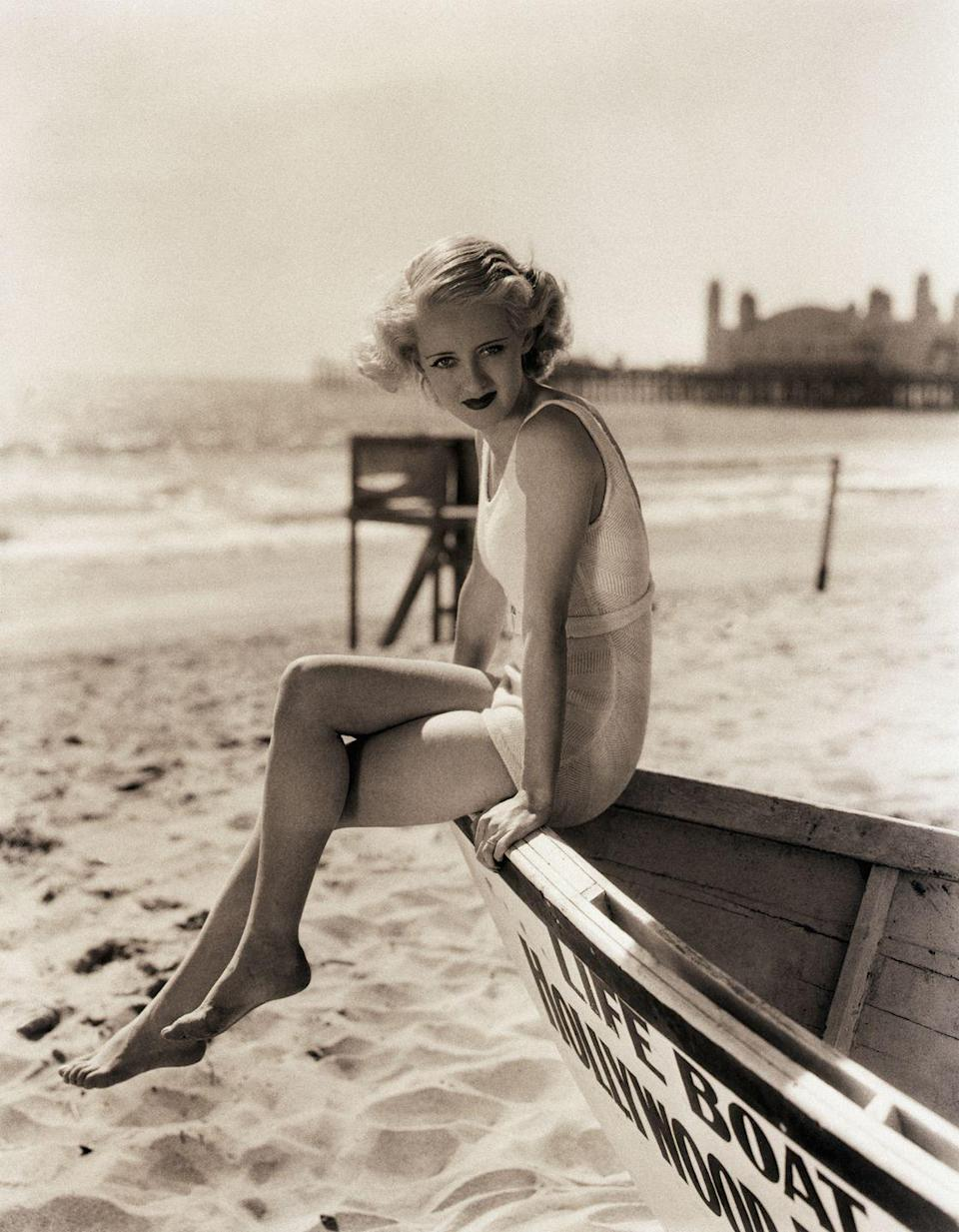 <p>Although Bette Davis's boat is landlocked, the star still looks like a natural, as she poses on the bow in a one-piece bathing suit. </p>