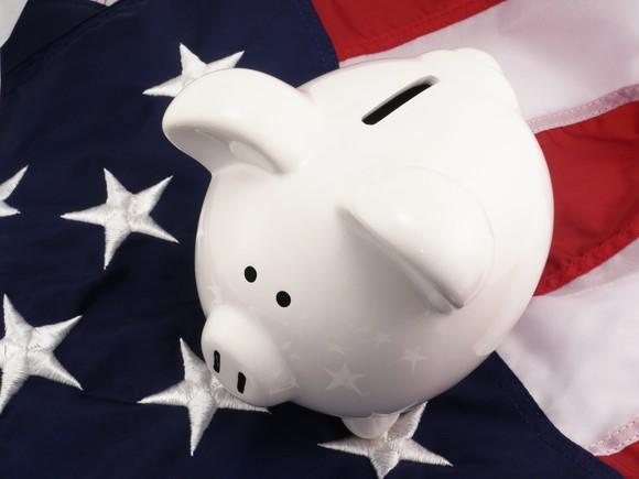 Piggy bank sitting on American flag