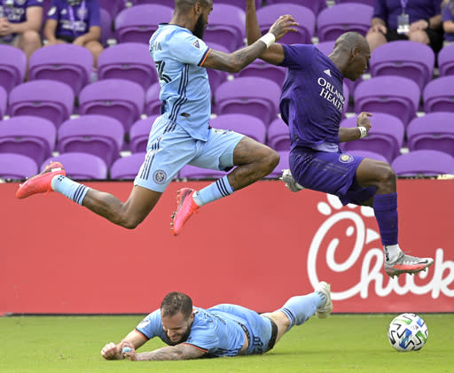 Orlando City defender Kamal Miller, right, jumps through the air as New York City FC defender Sebastien Ibeagha, left, and defender Maxime Chanot, below, defend during overtime of an MLS soccer playoff match, Saturday, Nov. 21, 2020, in Orlando, Fla. (AP Photo/Phelan M. Ebenhack)