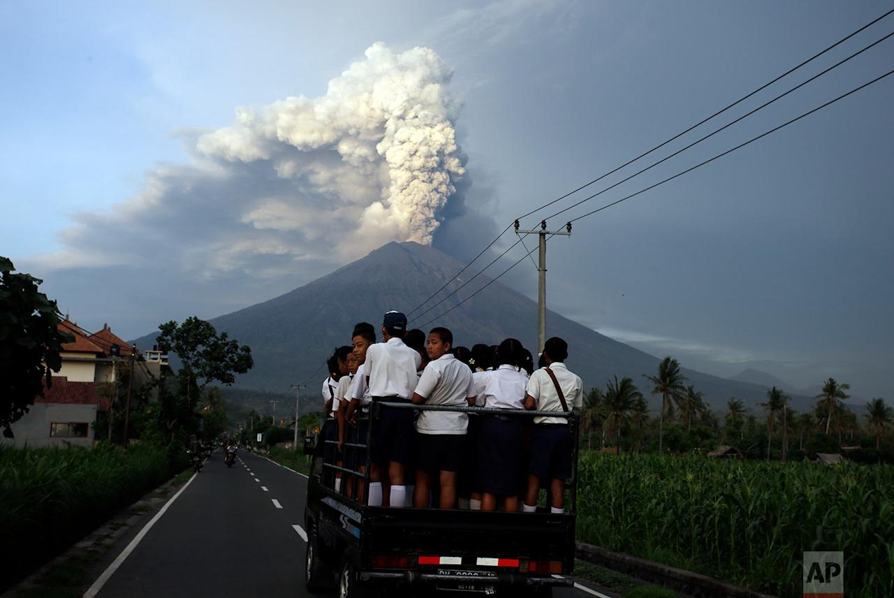 <p>School students stand on a truck as their transport to go to school with the Mount Agung volcano spews smoke and ash in Karangasem, Bali, Indonesia. Indonesia authorities raised the alert for the rumbling volcano to highest level on Monday and closed the international airport on the tourist island of Bali stranding some thousands of travellers.(AP Photo/Firdia Lisnawati) </p>