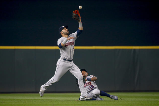 Houston Astros center fielder Tony Kemp (right) slides as he watches left fielder Marwin Gonzalez make a catch on a fly ball hit by Seattle Mariners' Robinson Cano during the third inning of a baseball game Tuesday, Aug. 21, 2018, in Seattle. (AP Photo/Jennifer Buchanan)