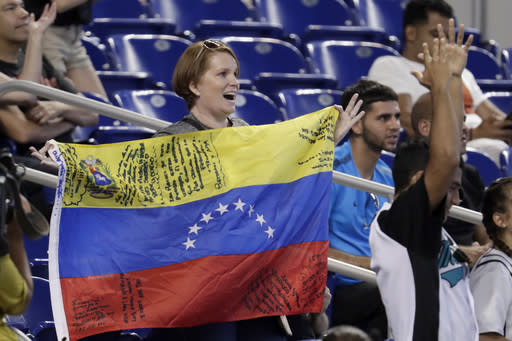 A fan waves a Venezuelan flag during a baseball game between the Miami Marlins and the Kansas City Royals, Sunday, Sept. 8, 2019, in Miami. (AP Photo/Lynne Sladky)