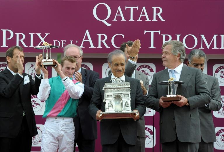 Racing great - Prince Khalid Abdullah (C) with jockey Ryan Moore (2L) and trainer Michael Stoute (R) after Workforce's victory in the 2010 Prix de l'Arc de Triomphe