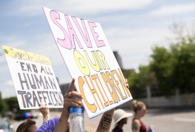 """People march during a """"Save the Children"""" rally outside the Capitol building on August 22, 2020 in St Paul, Minnesota. Hundreds of rallies around the country, meant to decry human trafficking and pedophilia, are scheduled for today, some of which have been linked to social media accounts promoting the QAnon conspiracy."""