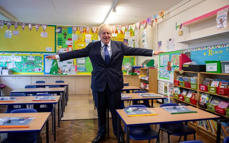 Britain's Prime Minister Boris Johnson gestures as he visits St Joseph's Catholic School and meets with the headteacher, Bernadette Matthews - Lucy Young/Pool