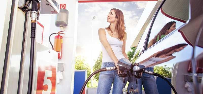 Woman pumping gas a gas station.
