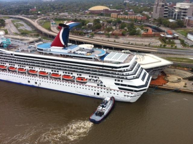 A tug vessel pushes the Carnival Triumph to moor at the Signal International shipyard on the Mobile River, April 3, 2013. The cruise ship broke loose from a BAE Systems dry dock after strong winds from a storm. (U.S. Coast Guard photo)