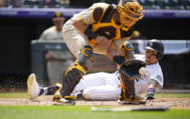 Colorado Rockies' Yonathan Daza, right, scores on a double hit by Trevor Story as San Diego Padres catcher Webster Rivas, left, fields the throw in the fourth inning of a baseball game Wednesday, June 16, 2021, in Denver. (AP Photo/David Zalubowski)