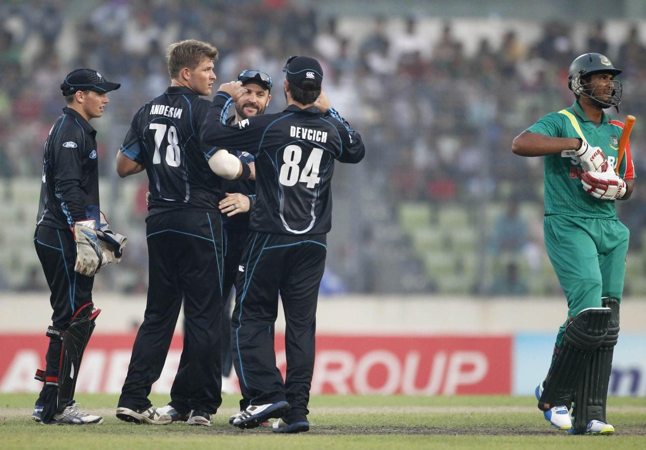 Bangladesh's Mahmudullah (R) leaves the field as New Zealand's fielders celebrate his dismissal during their second one-day international (ODI) cricket match in Dhaka October 31, 2013. REUTERS/Andrew Biraj (BANGLADESH - Tags: SPORT CRICKET)