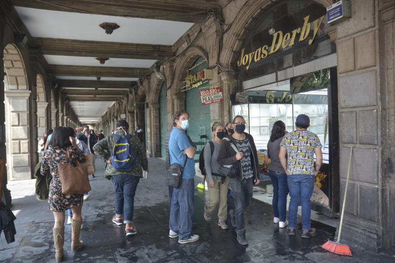 MEXICO CITY, MEXICO - JUNE 30: People wait to enter a jewelry store during the reopening of the Historic Center after three months on June 30, 2020 in Mexico City, Mexico. As ICU occupancy trends downward, authorities downgraded the alert level from red to orange in Mexico City. Economic activity starts reopening gradually following a staggered schedule, with restrictions and preventive measures. (Photo by Medios y Media/Getty Images)