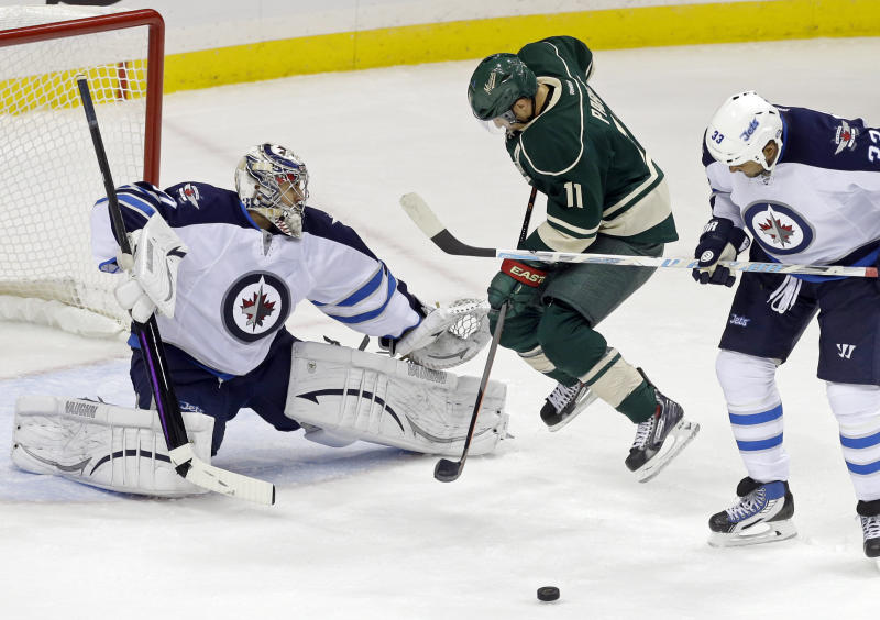 Minnesota Wild's Zach Parise, center, jumps clear as his shot is blocked by Winnipeg Jets goalie Ondrej Pavelec, left, of the Czech Republic, as Jets' Dustin Byfuglien, right, defends in the first period of an NHL hockey game on Thursday, Oct. 10, 2013, in St. Paul, Minn. (AP Photo/Jim Mone)