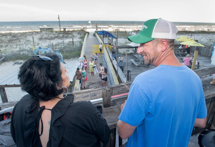Soula and Bryce Gallatin, of Columbia, Mo., hang out on the back deck of the Flora-Bama Lounge overlooking the Gulf of Mexico in Perdido Key, Fla., on Wednesday, June 19, 2019.