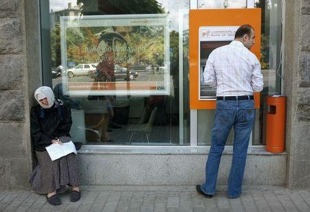 A man uses an automated teller machine next to a woman begging for money on the street in the Georgian capital Tbilisi