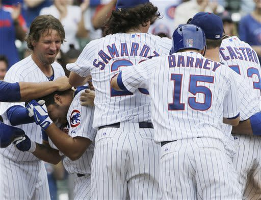 Chicago Cubs' Dioner Navarro, lower left, celebrates with teammates after hitting a game-ending sacrifice fly during the 11th inning of a baseball game against the Pittsburgh Pirates in Chicago, Sunday, July 7, 2013. The Cubs won 4-3. (AP Photo/Nam Y. Huh)