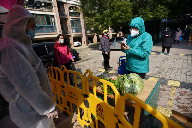 FILE PHOTO: Resident uses a mobile phone to pay for vegetables purchased through group orders at a collection point set up at the entrance of a residential compound in Wuhan