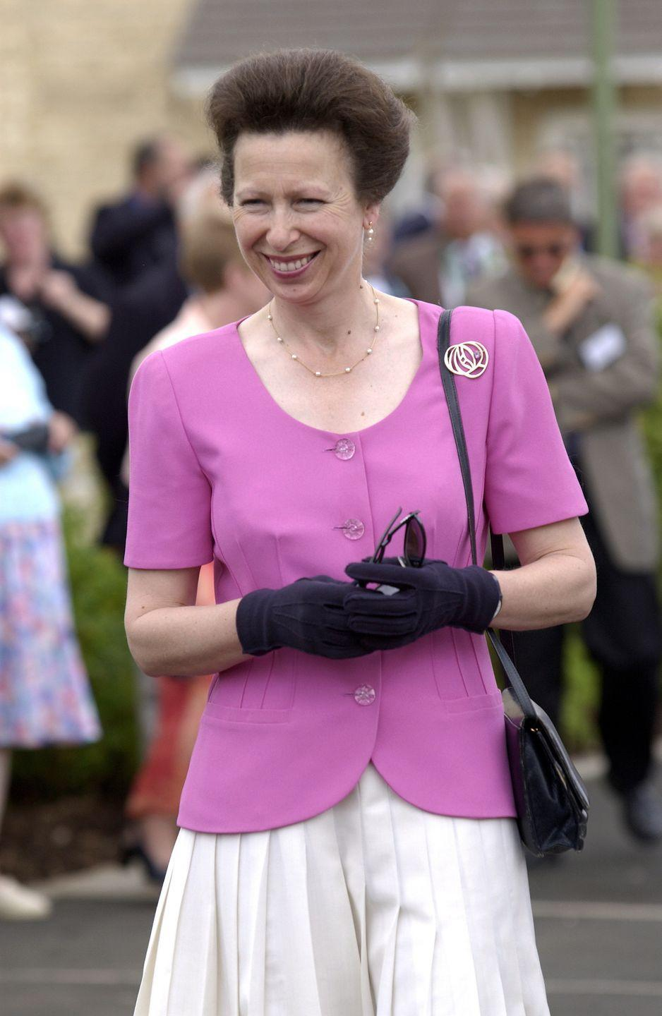 <p>Princess Anne sported this ladylike pink top and white skirt combo to visit an urban housing project in Oxfordshire in 2001. </p>