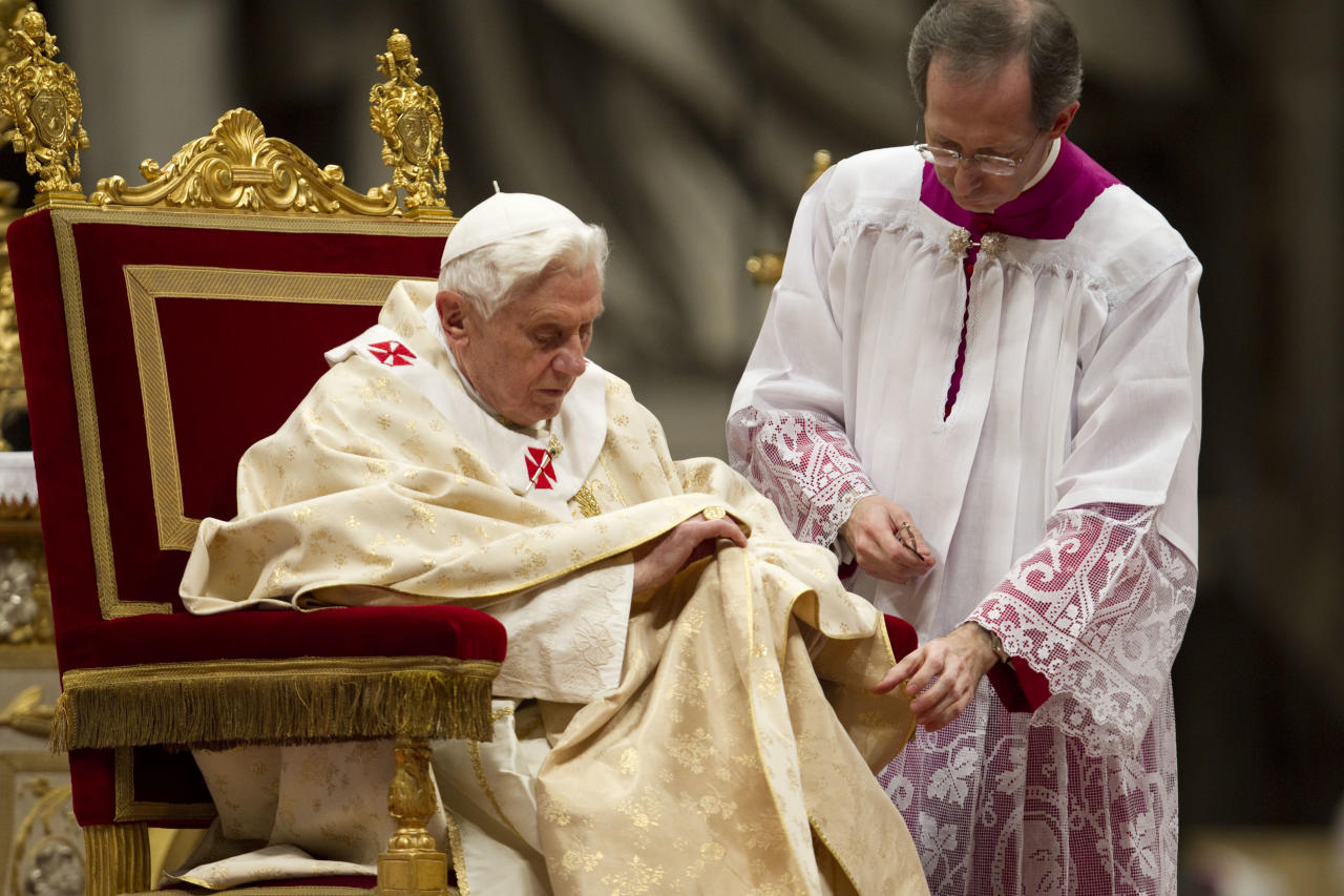 Pope Benedict XVI is heped by his aide Guido Marini as he celebrates Christmas Mass in St. Peter's Basilica at the Vatican, Saturday, Dec. 24, 2011. (AP Photo/Andrew Medichini)
