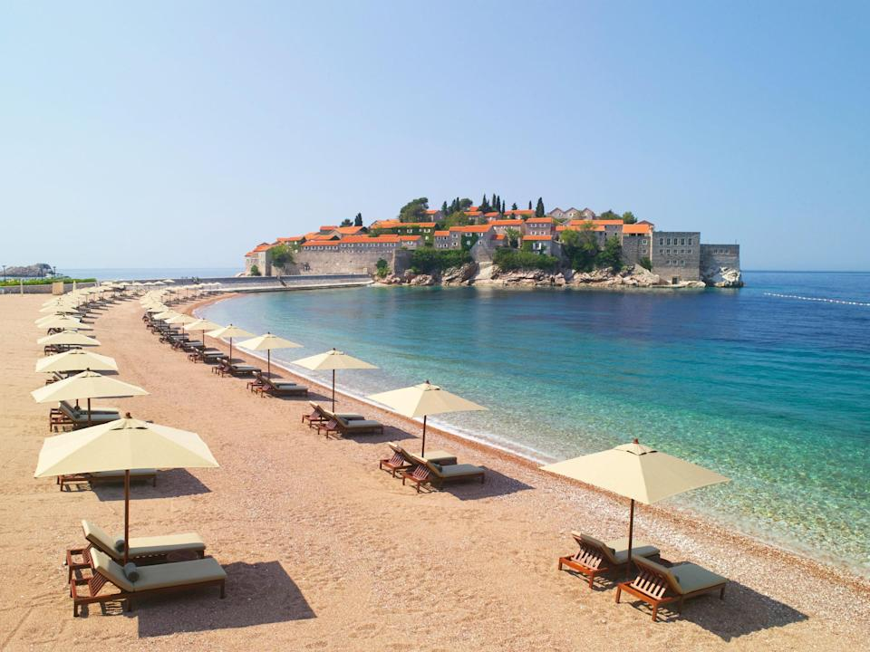 """A playground for celebrities like Elizabeth Taylor, Sophia Loren, and Kirk Douglas in the 1960s, Sveti Stefan today is off-limits to anyone not staying at the luxurious <a href=""""https://www.cntraveler.com/hotels/montenegro/s-stefano/aman-sveti-stefan?mbid=synd_yahoo_rss"""" rel=""""nofollow noopener"""" target=""""_blank"""" data-ylk=""""slk:Aman resort"""" class=""""link rapid-noclick-resp"""">Aman resort</a> on the islet. The beach shares a name with the onshore township connected to the island by a causeway, and is one of the most photographed spots in Montenegro."""