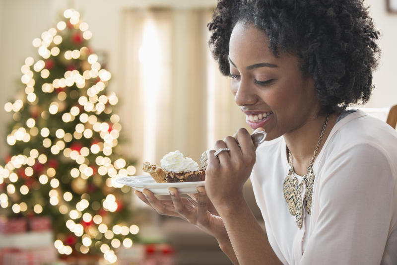 Mixed race woman eating dessert by Christmas tree