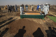 Funeral home workers in a protective suit lower into ground a coffin carrying Duduzile Margaret Mbonane, who died from COVID-19, during her funeral in Thokoza east of Johannesburg, South Africa, Thursday, July 23, 2020. Mbonane died just a month before her retirement, her husband said. Those on the front lines have been hit hard: The World Health Organization said Thursday more than 10,000 health workers have been infected in its African region, which is largely sub-Saharan Africa. (AP Photo/Themba Hadebe)