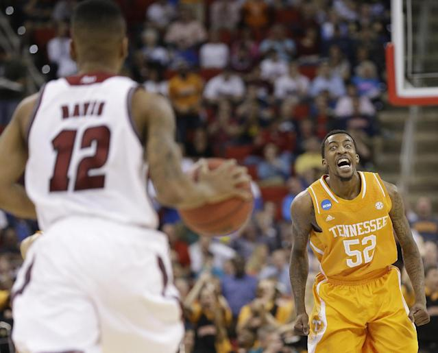 Tennessee guard Jordan McRae (52) watches Massachusetts guard Trey Davis (12) come down the court during the first half of an NCAA college basketball second-round tournament game, Friday, March 21, 2014, in Raleigh. (AP Photo/Gerry Broome)
