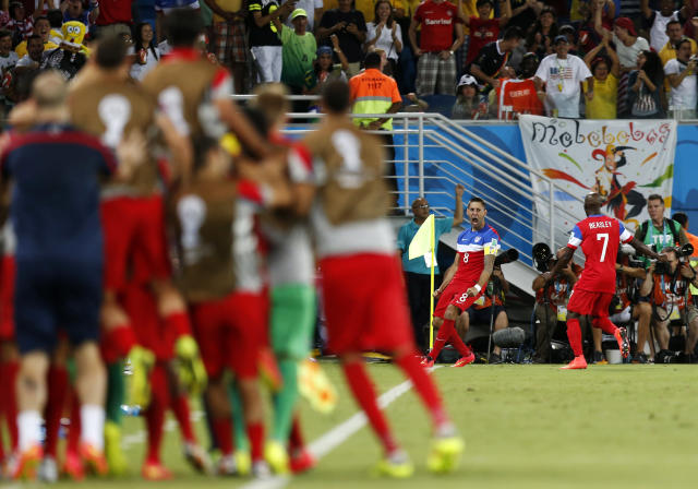 United States' Clint Dempsey (8) celebrates with DaMarcus Beasley (7) after scoring his side's first goal during the group G World Cup soccer match between Ghana and the United States at the Arena das Dunas in Natal, Brazil, Monday, June 16, 2014. (AP Photo/Julio Cortez)