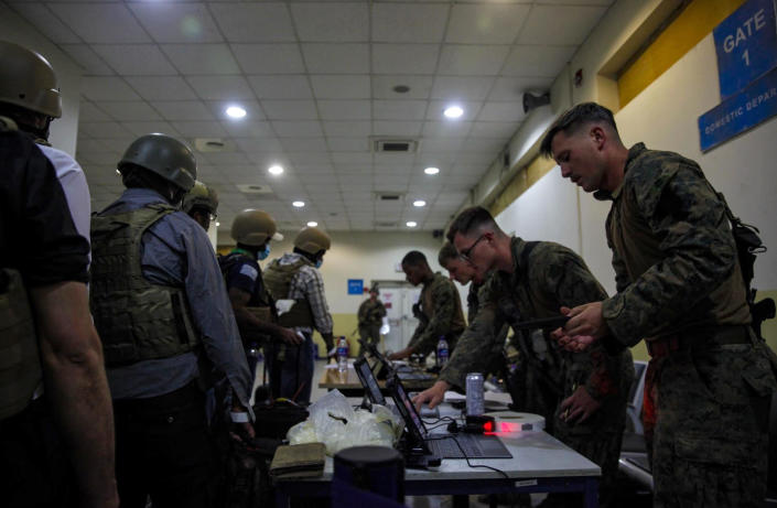Marines of the 24th Marine Expeditionary Unit (MEU) process Department of State personnel for evacuation at Hamid Karzai International Airport, in Kabul, Afghanistan, Sunday, Aug. 15, 2021. (Sgt. Isaiah Campbell/U.S. Marine Corps via AP)