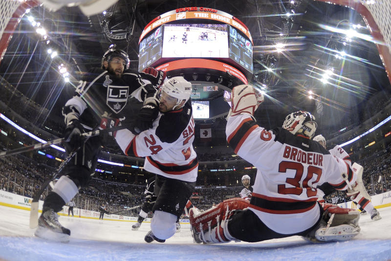 Los Angeles Kings center Jarret Stoll (28) and New Jersey Devils defenseman Bryce Salvador (24) collide as New Jersey Devils goalie Martin Brodeur (30) makes a save in the second period during Game 3 of the Stanley Cup Finals, Monday, June 4, 2012, in Los Angeles. (AP Photo/Harry How, Pool)