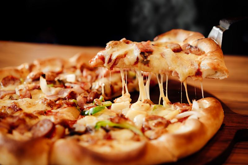 A hot slice of pizza is lifted from a pie.